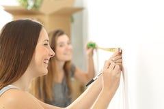 Compagnons de chambre mesurant et se déplaçant à la maison Photos stock
