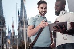 Compagnons de sourire partageant la vidéo sur la tablette dehors photo stock