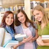 Compan@eros de clase de la High School secundaria con los libros de la biblioteca Foto de archivo