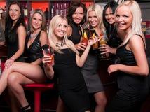 Companhia das meninas que tem o divertimento no clube de noite Fotos de Stock Royalty Free