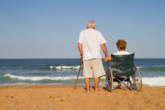 Companion. Life time companion concept: senior couple holding hands on beach, she is in wheelchair stock images