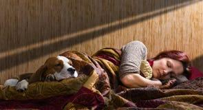Companion. The sleeping woman and its dog , focus on a dog Stock Image