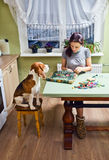 Companion. The dog looks as the mistress embroiders royalty free stock photos