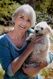 Companions. An attractive senior citizen lady with shiny white hair and a big smile, holding her companion pet doggie. Shallow depth of field Royalty Free Stock Photos