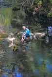 Companions in the Creek. A senior citizen lady with white hair relaxing on a large rock in the creek, playing with her pet doggies. Shallow depth of field. Copy Stock Photos