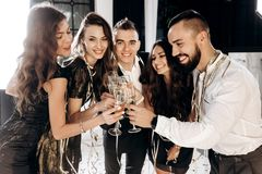 Company of beautiful young girls and guys dressed in stylish elegant clothes stand together and clink glasses with stock photo