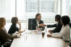 Company boss handshaking african american employee at corporate. Company boss handshaking african american worker at corporate group meeting, ceo welcoming new Royalty Free Stock Photography
