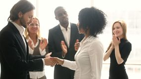 Company boss handshaking african employee, promoting congratulating black young woman. Company boss handshaking promoting african manager while colleagues stock video footage