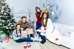 Company of boy and  three girls sitting near the Christmas tree Royalty Free Stock Image