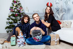 Company of boy and  two girls sitting near the Christmas tree in Royalty Free Stock Photo