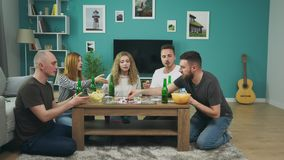 Company of boys and girls playing board game in living room and drinking beer.  stock footage