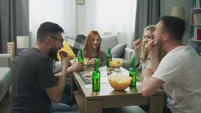 Company of boys and girls playing board game in living room and drinking beer.  stock video