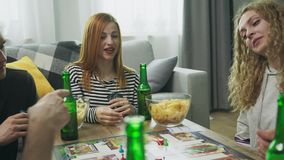 Company of boys and girls playing board game in living room and drinking beer stock video