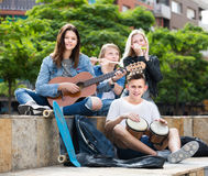 Company of carefree teenagers musicians. With instruments in park on summer day Royalty Free Stock Images