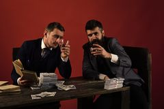 Company celebrates business profit, successful deal. Businessmen discussing illegal deal while drinking and smoking, red. Background. Men sitting at table with Royalty Free Stock Images