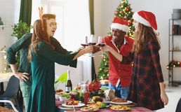 Company of cheerful and happy friends celebrating at the christmas dinner royalty free stock image