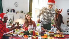 Company of cheerful and happy friends celebrating at the christmas dinner stock photo