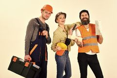 Company of cheerful workers, builder, repairer, plasterer. Man and woman with smiling faces in helmet and boilersuit. Company of cheerful workers, builder stock photography