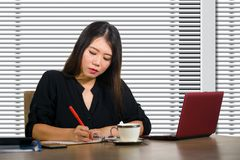 Company corporate portrait of young beautiful and busy Asian Chinese woman working busy at modern office computer desk by venetian stock photos