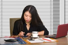 Company corporate portrait of young beautiful and busy Asian Korean woman working busy at modern office computer desk by venetian royalty free stock photo