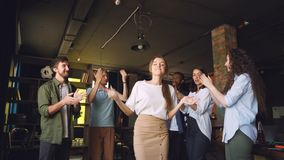 Company employees are dancing at corporate party in modern loft style office, attractive young men and women are having