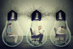 Company employees sitting in row inside electric lamp light bulb using laptop Royalty Free Stock Photography