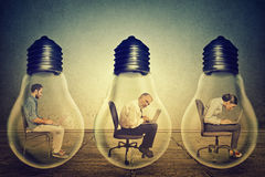 Company employees sitting in row inside electric lamp using working on computer Stock Image