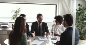 Company executive motivating diverse team giving high five at meeting