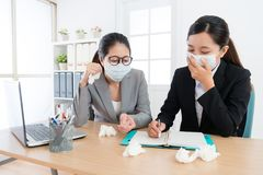 Company female worker having teamwork meeting. Young pretty company female worker having teamwork meeting and wearing medical mask discussing together when one Royalty Free Stock Photography