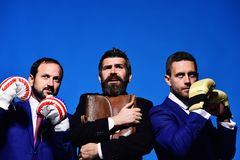 Company fights for business leadership. Businessmen and worker. With strict and scared faces on blue background. Business conflict concept. Bosses wear boxing stock photo