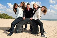 Company of five young friends at the seaside. Company of five teenage friends on the beach Stock Photo