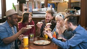 Company of five young hipster friends clinking peace of pizza in the stylish bar, pub. stock video footage