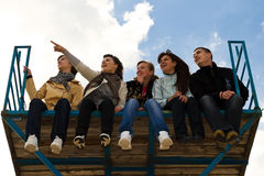 Company of five young people sitting together. Group of five teenage friends sitting together on high platform Royalty Free Stock Photo