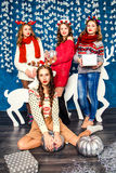 The company of four beautiful girls on the background of Christm Royalty Free Stock Image