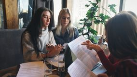 A company businesswomen actively discusses a business project in a cafe. A company of four businesswomen actively discusses a business project in a cafe stock video footage
