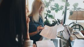 A company businesswomen actively discusses a business project in a cafe and signs a contract. A company of four businesswomen actively discusses a business stock footage