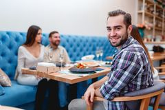 A company of young people spend time in a cafe chatting, and one guy smiles at the camera. stock image