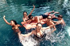 Company of friends carefree spend time swimming in pool. Swimming pool party concept. Guys and girls are resting on pool stock image
