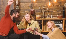 Company of friends celebrate with mulled wine in cozy atmosphere, wooden background. Cheers concept. Man and ladies on. Cheerful faces have fun together stock photo