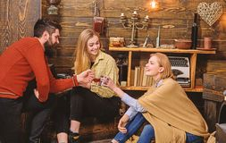 Company of friends celebrate with mulled wine in cozy atmosphere, wooden background. Man and ladies on cheerful faces. Have fun together. Cheers concept stock photos
