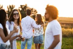 Company of friends chatting in the open air on a sunny day. In the background a young man embraces a girl. stock images