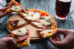 Company of friends eating homemade pizza, close up. People takin. G pizza slices from the plate. Party, dinner, eating concept stock photos
