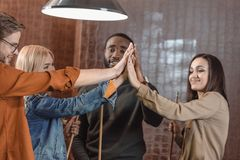 Company of friends holding cues and giving high five to each other. At bar stock image