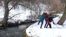 A company of friends play and make selfies by the river in winter stock video footage