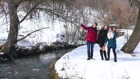 A company of friends play and make selfies by the river in winter stock footage