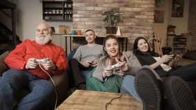 Company of friends plays video game together. Company of friends are playing video game together sitting at bean bags at home. Cheerful people relax and spend stock footage