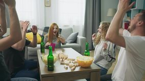 A company of friends plays a wooden tower in a cozy living room stock footage