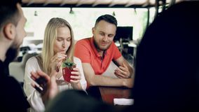 Company of friends sitting at a bar counter in summer day. Beautiful girl taking from table and tasting fresh cocktail. Company of friends are relaxing in a stock footage