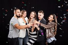 Company of friends in stylish casual clothes stand together and clink glasses with champagne on a black background and royalty free stock photos