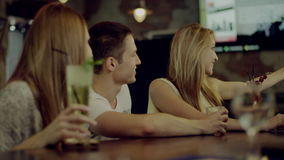 Company of friends taking selfie. Company of friends of two women and a man taking selfie sitting with cocktails in a bar stock video